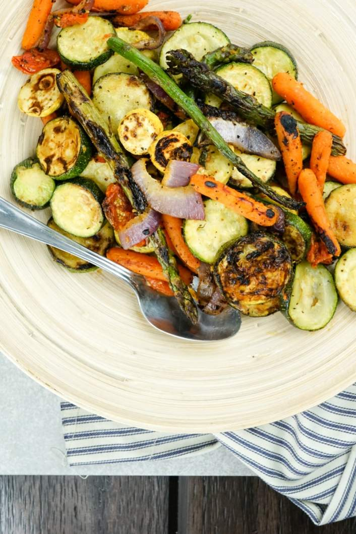 Grilled vegetables ready to be served on a platter with a spoon.