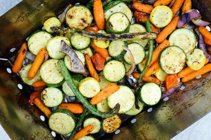 Grilled Vegetables in a grill basket after 15 minutes of cooking.
