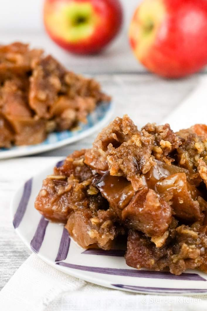 Slow Cooker Apple Crisp served on a plate with apples in the background.