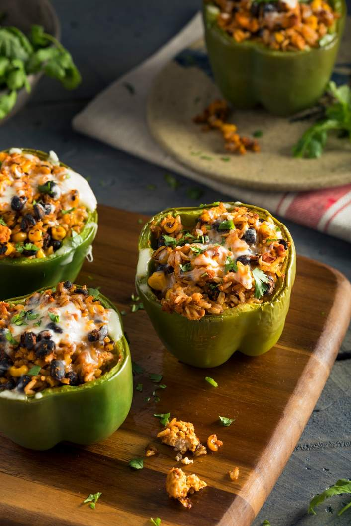 Slow cooker vegetarian stuffed peppers with cilantro and cheese on a dark background.