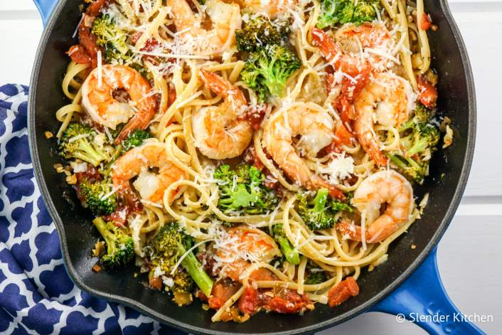 Pasta with lemon, broccoli, tomatoes, and shrimp in a pan.