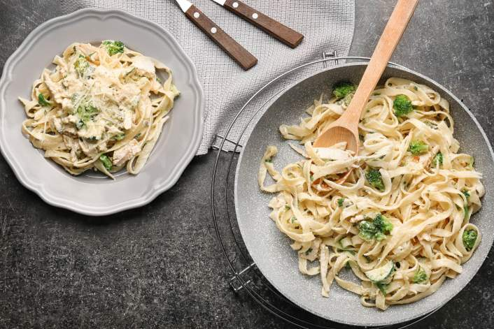 Creamy pasta with broccoli on two plates.