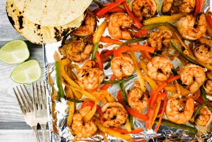 Easy sheet pan dinner of shrimp, peppers, and onions.
