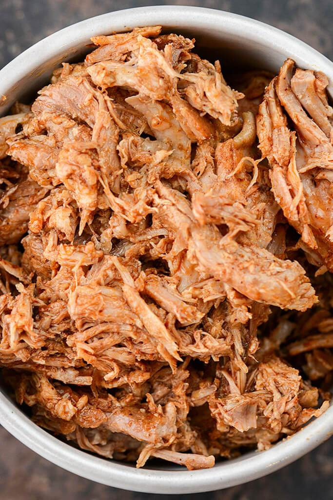 Gray bowl filled with shredded seasoned cooked Mexican style pork.