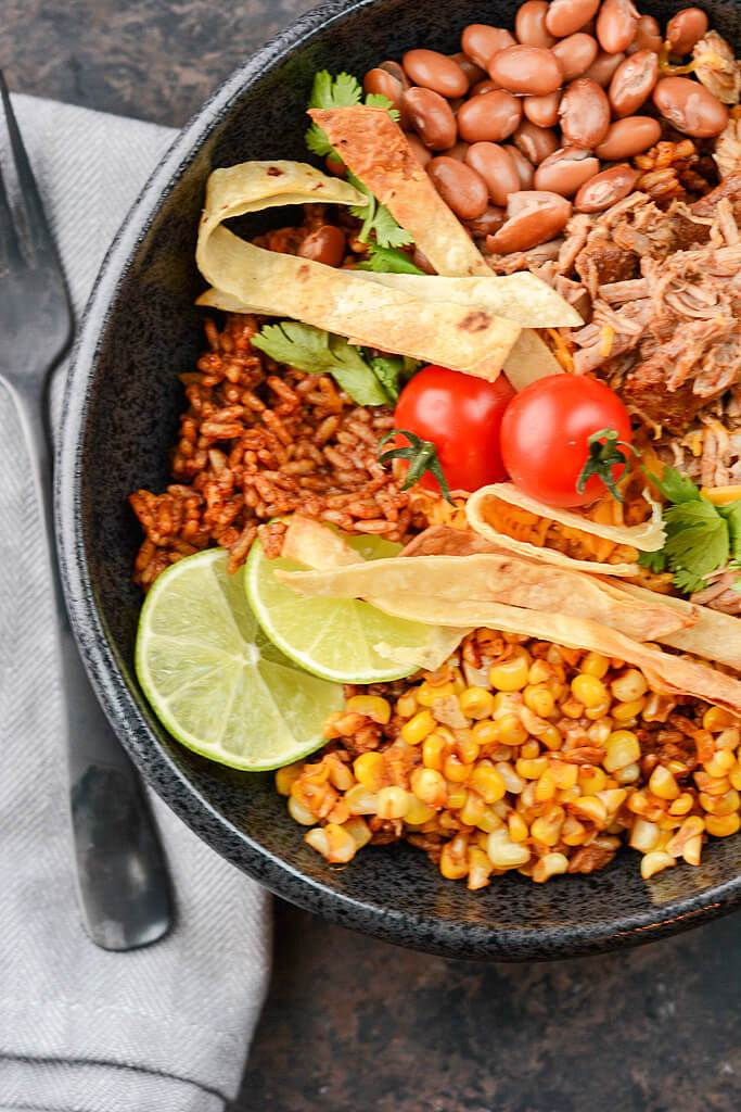 Overhead view of pulled Pork over rice with corn and beans in black bowl topped with limes and tomatoes.