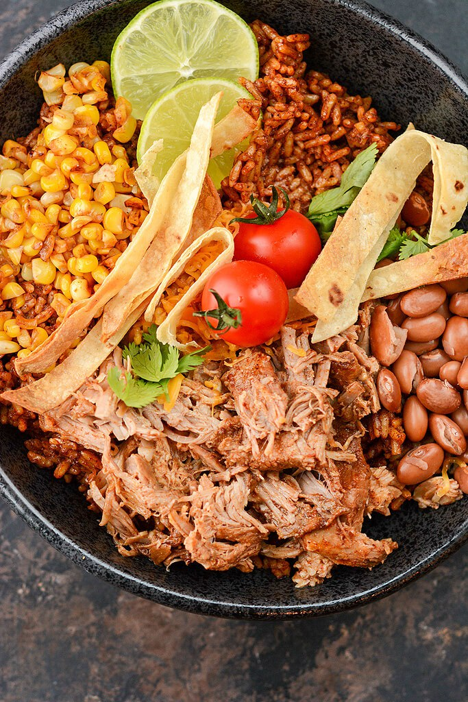 Pulled Pork over rice with corn and beans in black bowl topped with limes and tomatoes.