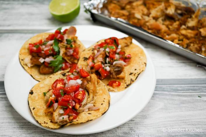 Slow Cooker Chicken Carnitas with lime juice and pico de gallo.