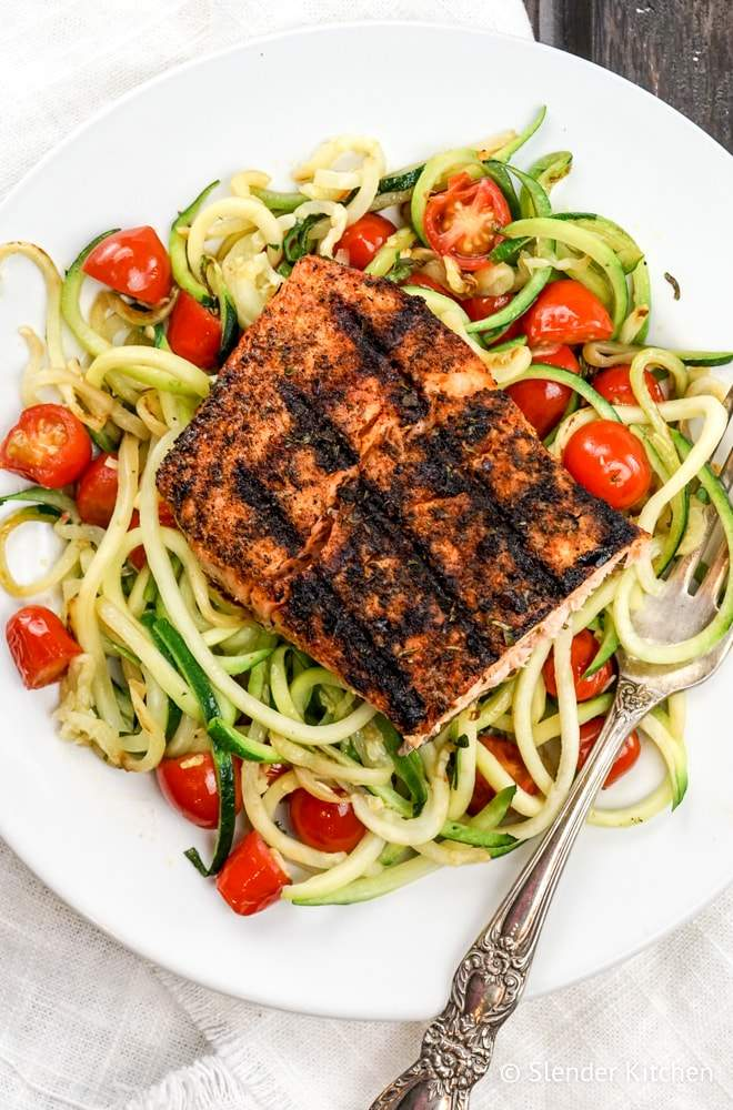 Blackened Salmon with Garlic Zucchini Noodles on a plate with tomatoes.