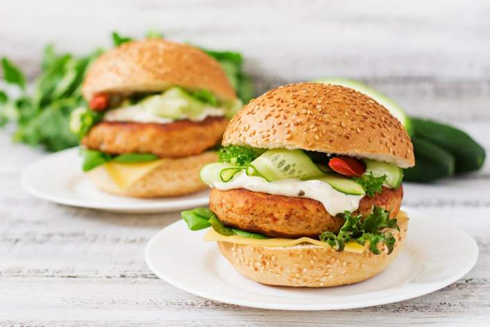 Two Tilapia Fish Burgers with greens and cucumber.