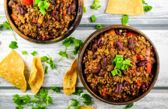 Turkey chili in two wooden bowls with chips and cilantro.