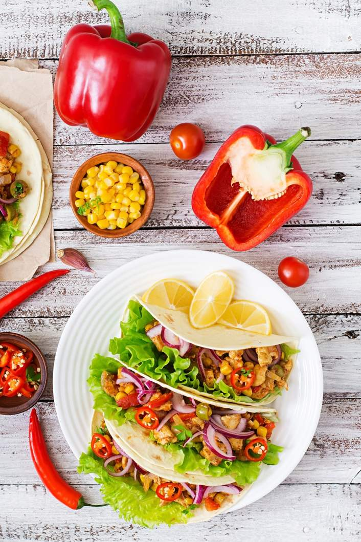 Spicy Chicken Tacos with corn on a white background with fresh produce.