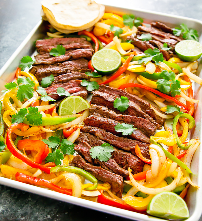 Steak fajitas made on a sheet pan with peppers and onions.