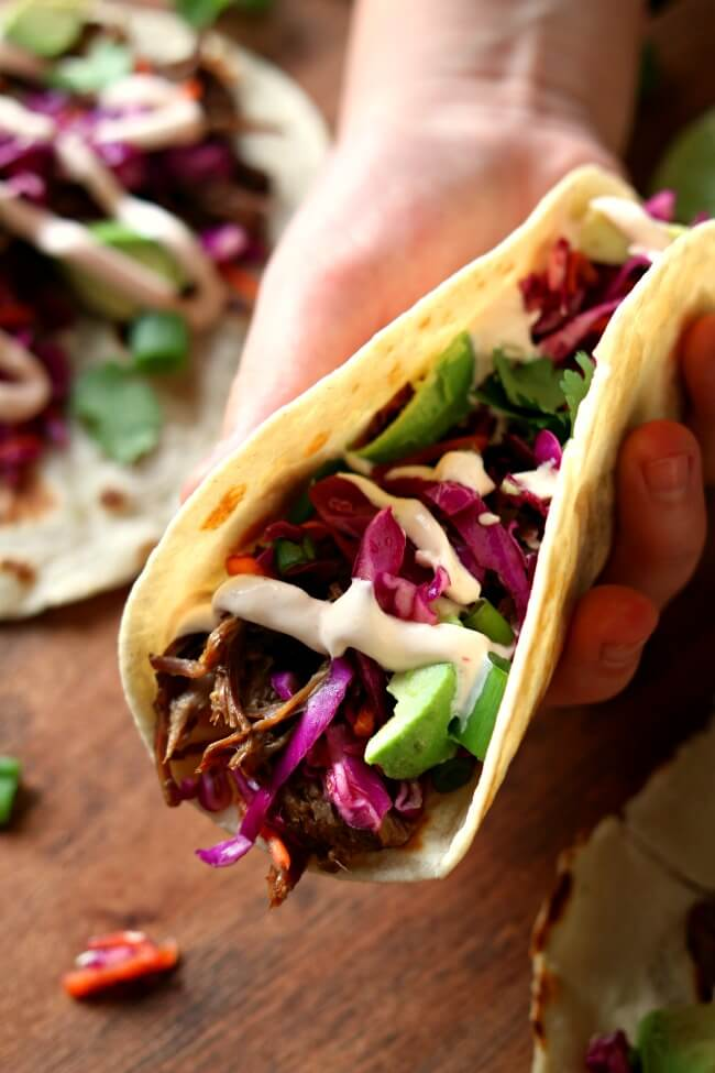 Pressure Cooker/Slow Cooker Korean Beef Tacos--tender shredded seasoned beef is rolled up in a warm tortilla with crunchy cabbage, diced avocado, chopped cilantro, sriracha sour cream and a splash of roasted garlic seasoned rice vinegar. When you bite into this taco it's like a party in your mouth. All the flavors and textures come together in a perfect union.