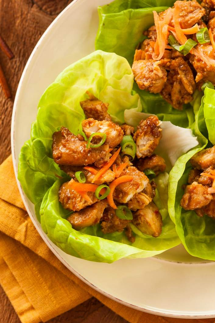Crockpot Korean Chicken on a plate with lettuce and carrots.