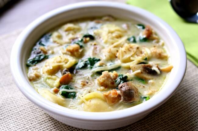 """Instant Pot Tortellini Soup with Parmesan, Chicken Sausage and Mushrooms needs to make its place on your menu this week. My husband said """"this is maybe the best soup I've ever had!"""" It's slightly creamy (but doesn't go overboard with dairy) and has amazing flavor thanks to the chicken sausage. It also has a nice pop of color from the chopped spinach. This soup can be made in minutes with your electric pressure cooker."""