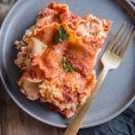 3 Ingredient Slow Cooker Lasagna on a gray plate with a gold fork topped with parsley