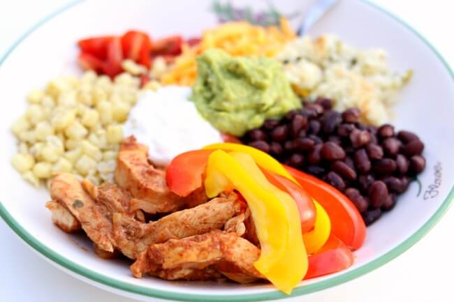 Instant Pot Chicken Fajita Bowls--the pot-in-pot cooking method allows you to cook cilantro lime rice, seasoned chicken, onions and bell peppers all together and in just a few minutes in your electric pressure cooker. Then they are layered in a bowl with cheese, sweet corn, tomatoes, black beans, sour cream and guacamole. It's definitely a fiesta in your mouth.