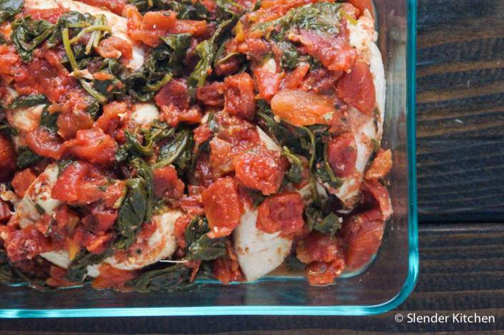 Healthy Crockpot Tomato Balsamic Chicken with spinach in a glass baking dish.