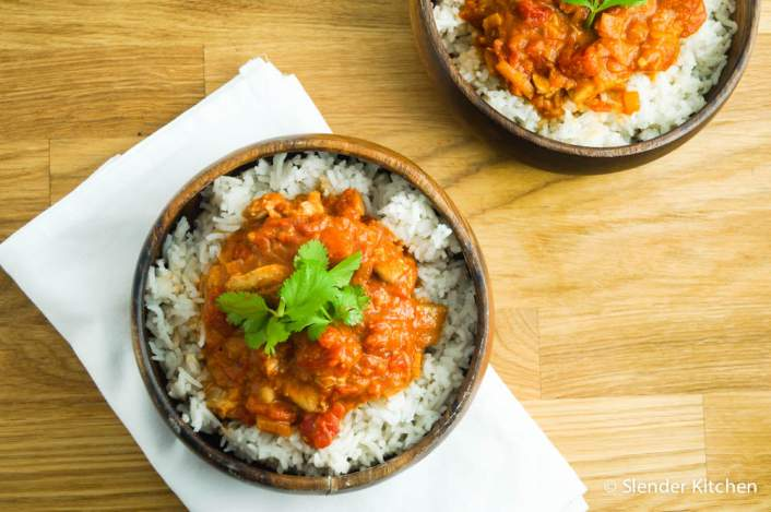 Healthy slow cooker chicken tikka masala in a wooden bowl.