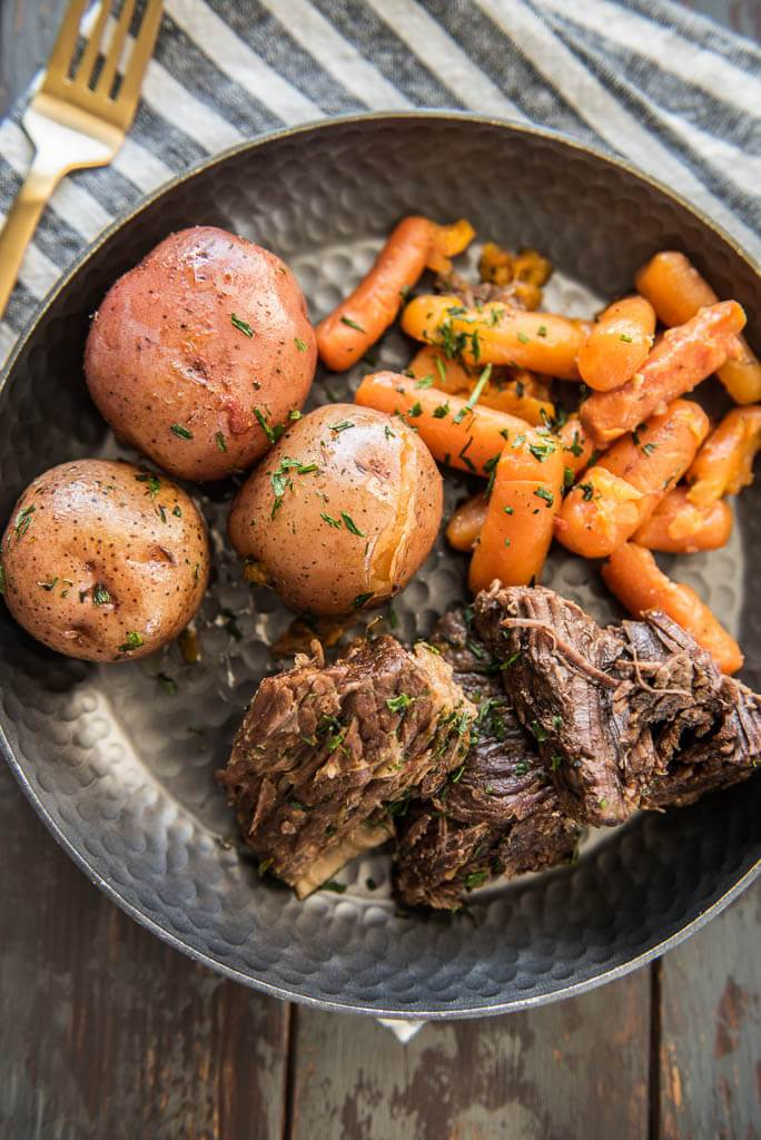 Pressure Cooker Pot Roast on a metal plate served with carrots and potatoes on a table with a gray and white napkin and gold fork