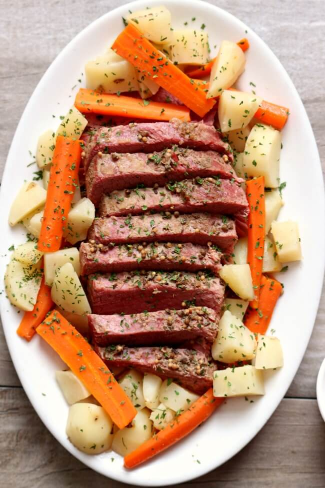 Instant Pot Corned Beef with Potatoes and Carrots--a super easy (and delicious) method for making corned beef! Tender corned beef is sliced and served alongside carrots and potatoes (and if you want, cabbage). A perfect dinner for St Patrick's Day (or any other day).