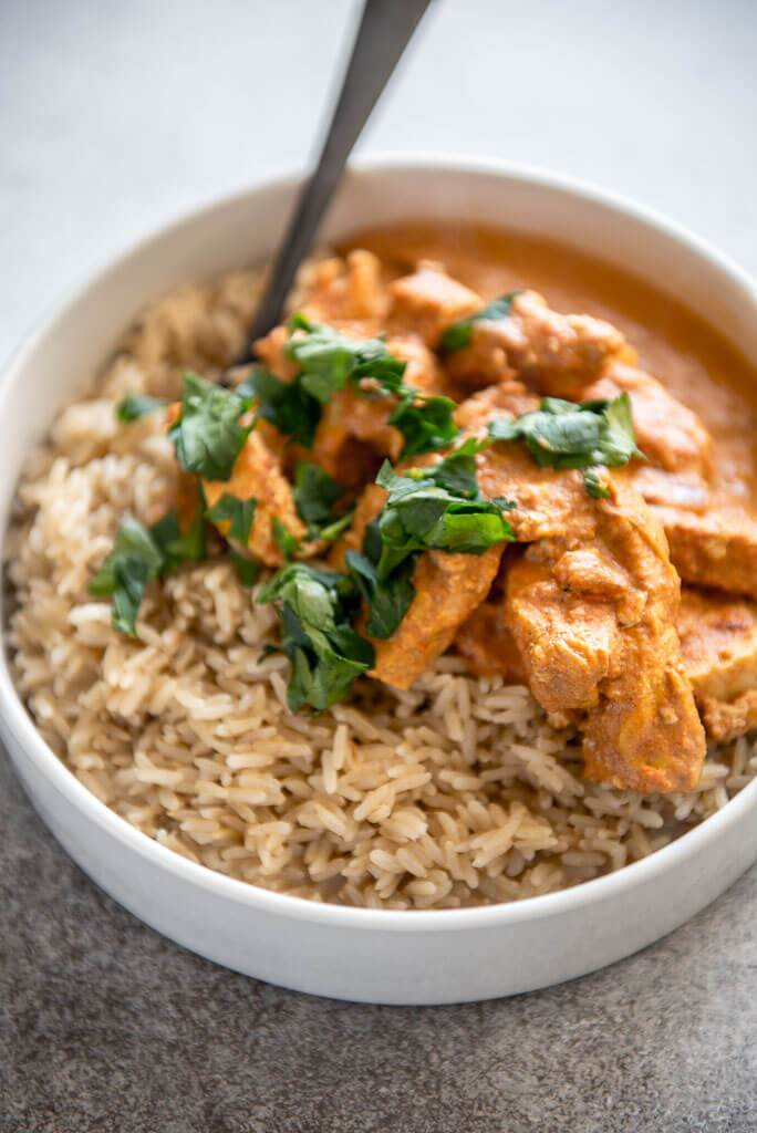 Instant Pot Chicken Tikka Masala in white bowls with brown rice and cilantro