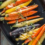 Multi-color oven roasted carrots on black serving platter topped with fresh thyme