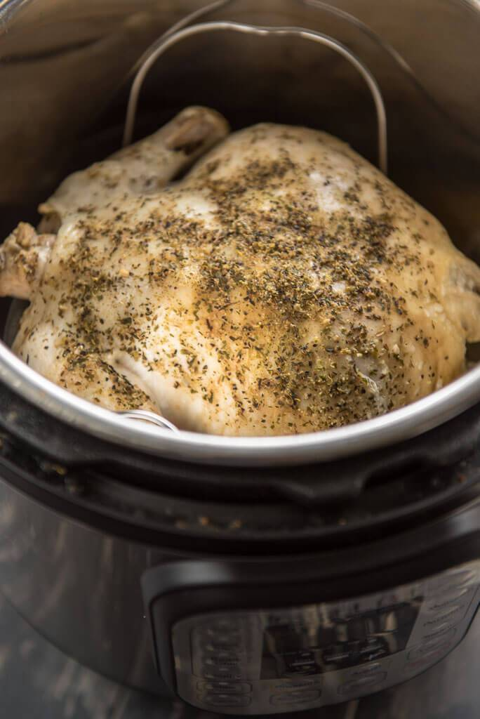 whole chicken on trivet in Instant Pot with seasonings