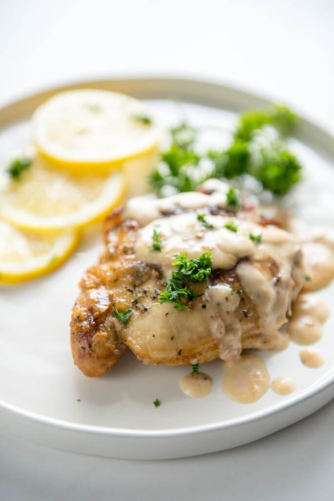 Slow Cooker Chicken Thighs with Creamy Lemon Sauce on white plate with sliced lemons