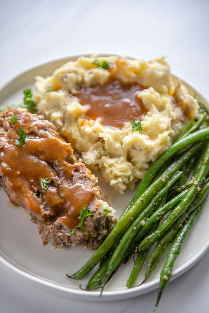 Slow Cooker Meatloaf with Buttermilk Mashed Potatoes on a white plate. Served with crispy garlic onion green beans on the side.