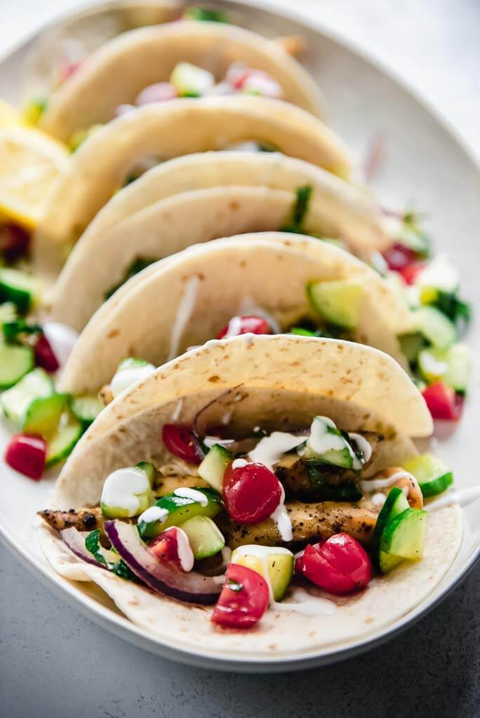 close up of greek chicken taco with cucumbers and tomatoes