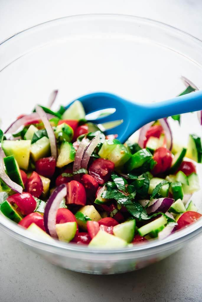 cucumber tomato and onion tossed together with a blue spoon in a glass bowl