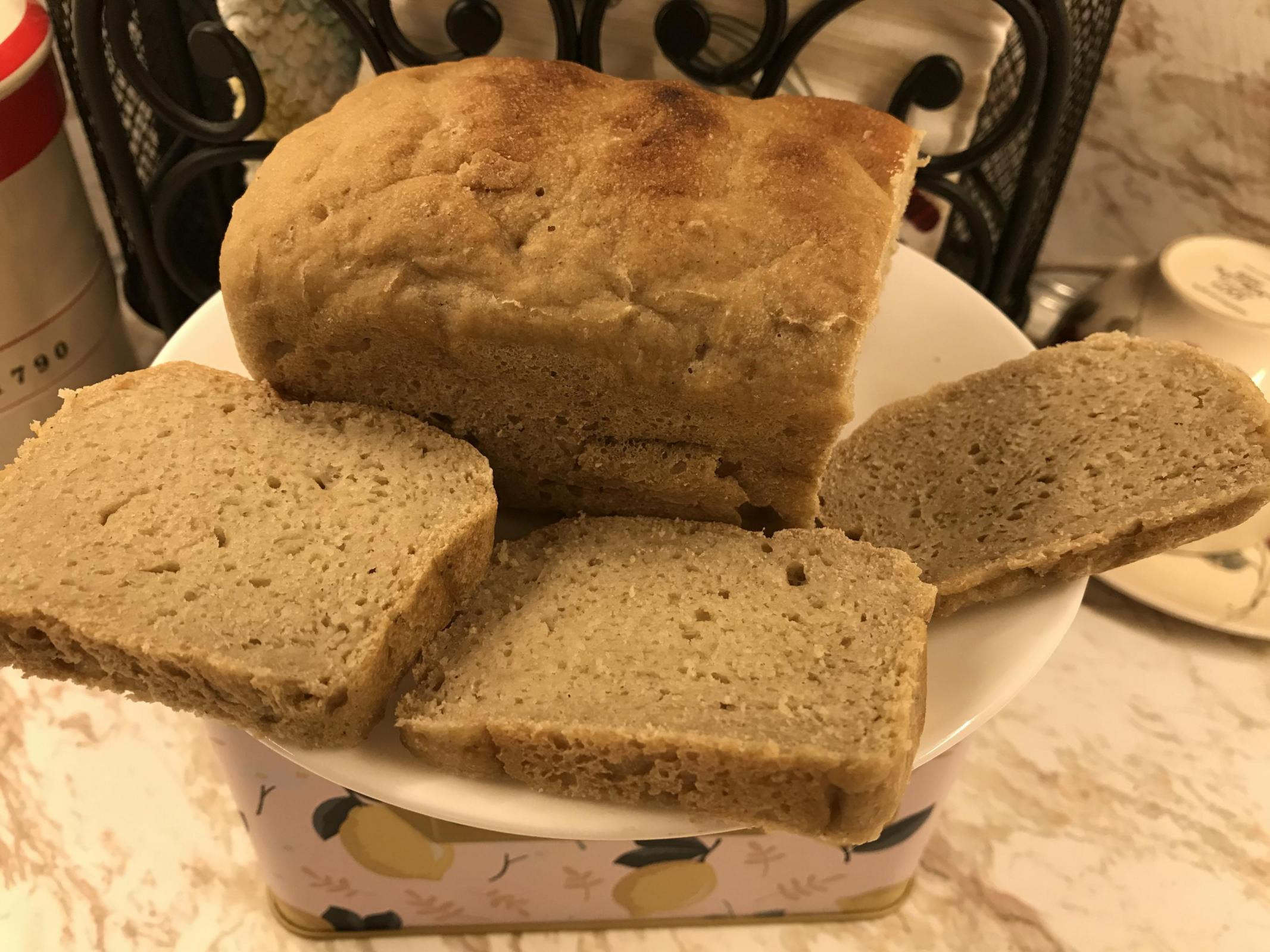 Bread loaf with three slices on plate.